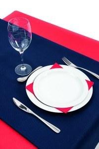 Combinación de mantel azul y servilleta lisa de papel de color rojo. Productos fabricados por Muropapel S.A